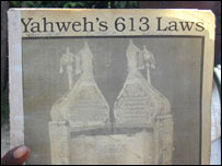 A sect member hold up a copy of Yahweh's 613 laws