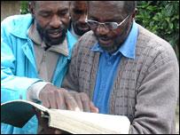 Miembros de la secta leyendo Libro de Yahweh.