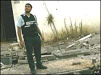 A policeman in Haifa looks up to the skies after a rocket strike
