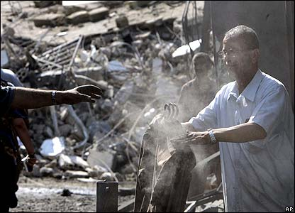 Woman looking at truck debris in Hadath