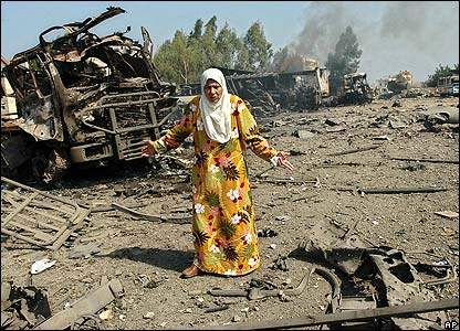 Woman looking at destroyed truck in Hadath