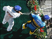 Kimi Raikkonen and Fernando Alonso spray champagne on a Formula One podium