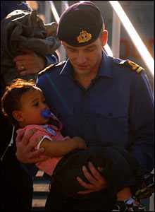 Sailor carrying young passenger off ship