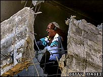 An Israeli man gestures in a damaged house after a Hezbollah missile strike in Haifa