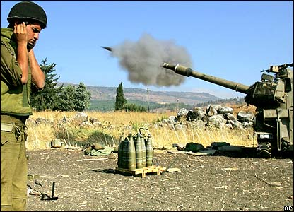 Israeli soldier next to tank firing missile