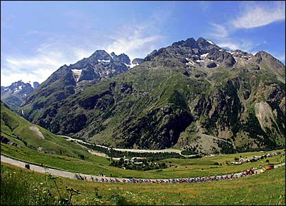 The peloton winds its way through the Alps