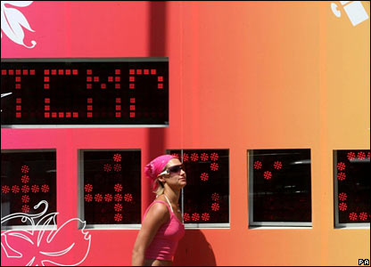 Woman walking past temperature gauge