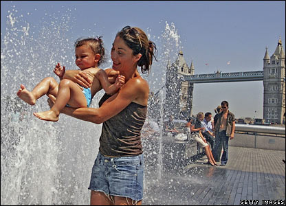 Mother and child playing in fountain near Tower Bridge, London