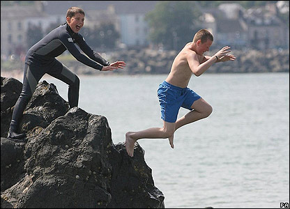 Children jumping off the rocks at Ballycastle