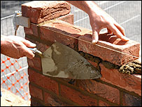 Builder laying bricks (BBC)