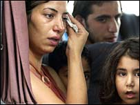 A Lebanese woman cries as she and her family flee the southern Lebanese city of Tyre