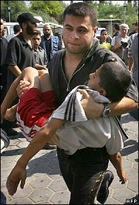 Palestinian man carries an injured boy to hospital in the central of Gaza Strip