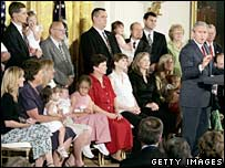 "President Bush (right) announces his veto surrounded by families with ""snowflake"" children"