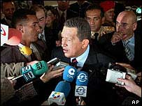 Venezuelan President Hugo Chavez surrounded by reporters