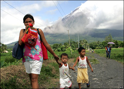 A mother leads her two children as smoke streams from the volcano