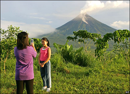 A mother takes a picture of her daughter with the volcano in the background