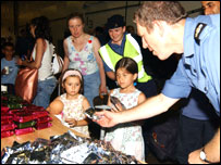 Children offered sweets by naval officer