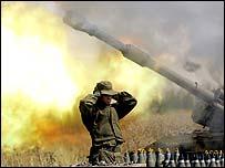 Israeli soldier covering ears near firing tank