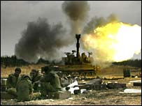Israeli soldiers sit as an artillery piece fires at targets in southern Lebanon from a position in northern Israel