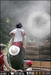A man holds his child in front of a giant spray near the Eiffel Tower in Paris