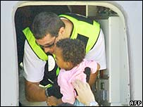 A Maltese policeman holding an Eritrean baby in a Spanish Air Force plane at La Valetta