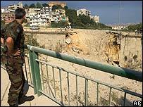 Ливанский солдат сморит на разрушенный мост в Бейруте