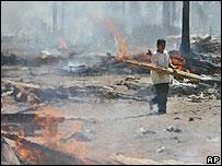 A tsunami survivor burns debris at a village in Pangandaran, West Java, Indonesia