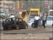 Iraqi police officers inspect a damaged vehicle at the site of multiple bomb explosions in east Baghdad on 22 July 2006
