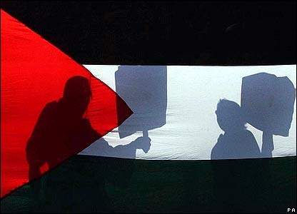 Protesters silhouetted by the Palestinian flag