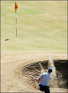 David Duval chips out of a bunker on the 18th hole