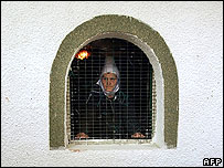 Ethnic Albanian woman looks out of window in Kosovo