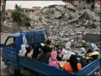 A family drives past rubble in Tyre