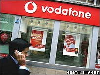 Man walking past a Vodafone shop