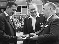 Jim Laker receives the two balls with which he claimed his 19 wickets at Old Trafford