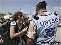 Fleeing tourists are helped by a soldier from the United Nations Truce Supervision Organization (UNTSO)