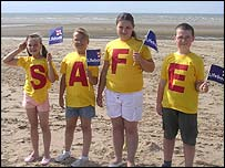 Children displaying Safe message