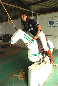 Victoria Grace demonstrates a polo swing from a wooden teaching horse