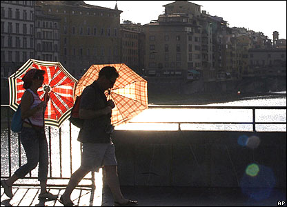 Passers-by protect themselves with umbrellas from the sun on the Arno river in Florence
