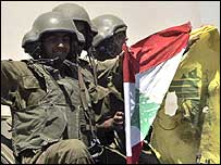Israeli soldiers with Lebanese and Hezbollah flags