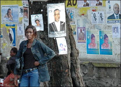 A woman stands by multiple posters in Kinshasa
