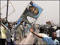 People pull down a poster of Mr Kabila in Kinshasa