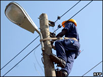 An electrician works on a street lamp in Monrovia