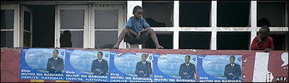 Children sit on a wall covered with election posters