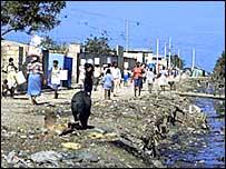 Gente caminando al costado de un hilo de agua en villa miseria. (Foto: Organización Panamericana de la Salud)