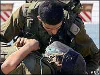 Israeli soldier talks to a wounded comrade