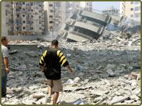 لبنانيان يسيران وأمامهما دمار أبنية هاجمتها القوات الإسرائيلية بالضاحية الجنوبية ببيروت، 27 يوليو/تموز 2006 - أسوشييتد برس