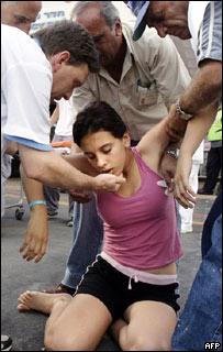 رجال يساعدون فتاة إسرائيلية على الإفاقة في بلدة نهاريا بعد تعرض قريتها لصاروخ أطلقه حزب الله من جنوب لبنان، 27 يوليو/تموز 2006