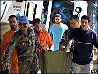 Медики несут тело убитого наблюдателя ООН