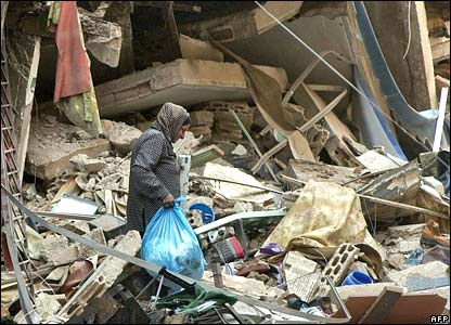 A Lebanese woman recovers belongings from the rubble of a destroyed southern Beirut neighbourhood