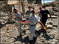 Rescue workers remove a body from the rubble in Kfar Joz following an Israeli strike